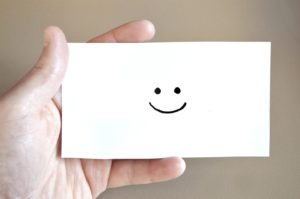 Hand holding a note with a smiley face