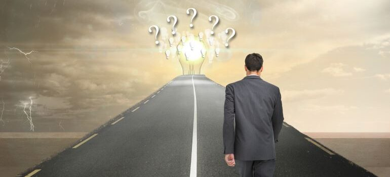 Businessman walking a pat toward ideas with questions marks.