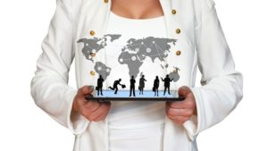 Business woman holding a pad with world map and business people connecting through online sales strategies for movers.