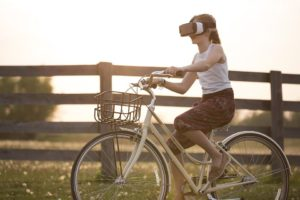 Girl riding a bicycle with a pair of VR glasses - nothing is impossible any longer in terms of software investment trends.