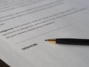 Signature field on a contract with a pen next to it.