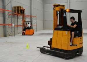 Two men driving forklifts in warehouse.