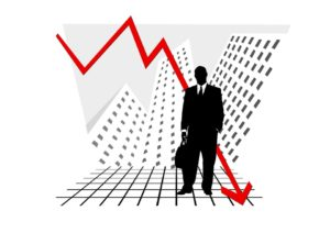 Businessman standing in front of a downward graph arrow.