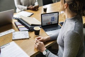 Women in an office, laptop with Business Plan on the table - expanding your business can start.