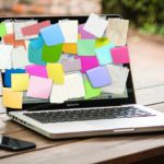 Countless sticky notes on a laptop screen.