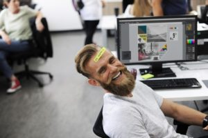 Guy sitting in office, laughing.