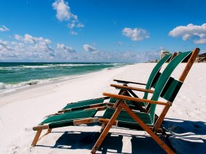 Two empty chairs on a beach.