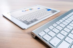 Tablet and keyboard with Google homepage.