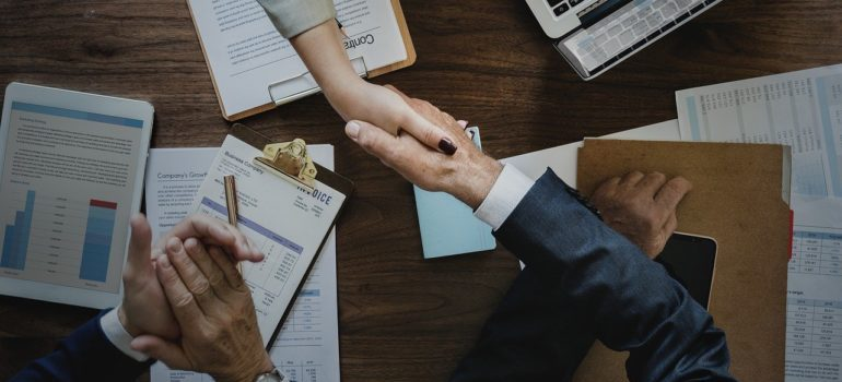 Handshake over a table with charts and contracts