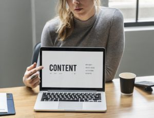 a girl pointing to the word content on the screen of her laptop