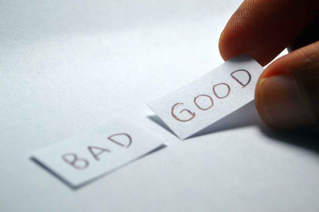 A hand picking a piece of paper with the word GOOD written on it. The word BAD on another piece of paper next to it.