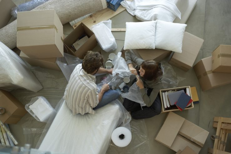Couple surrounded by boxes packing