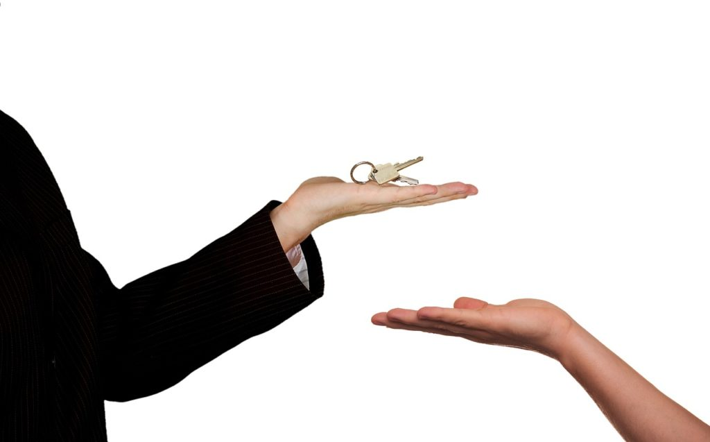 Person offering keys to other person