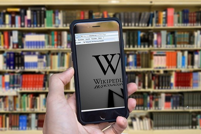 a person holding a phone with Wikipedia page, with a lot of books in te background, representing influence of Wikipedia in digital marketing
