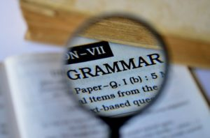 a magnifier showing the word GRAMMAR in a dictionary.