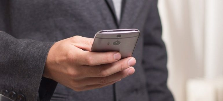 A man checking messages on his smartphone, whilst using one of the top social media tools.