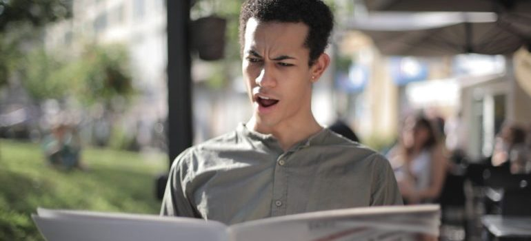 Person reading newspaper with shocked expression