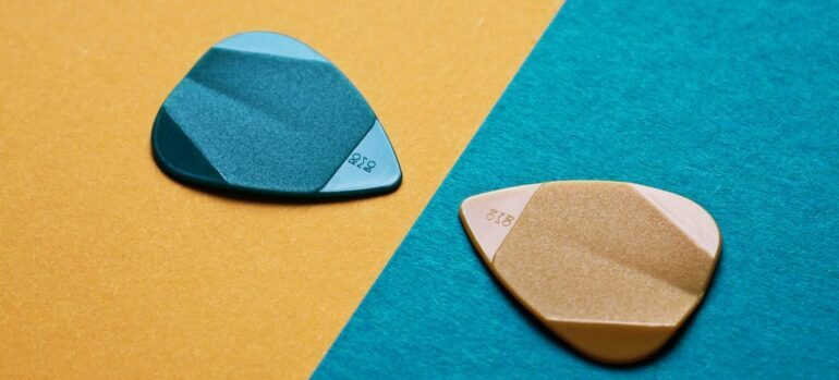 A pair of guitar picks on backgrounds of contrasting colors.