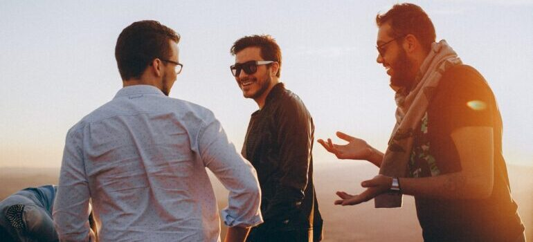 Three men standing outside and laughing.