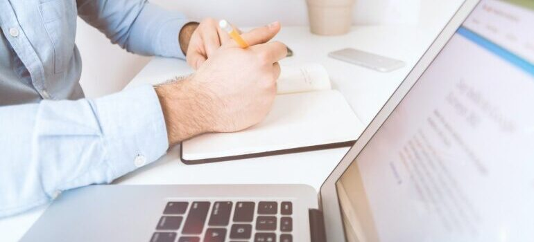 Image of person taking notes next to laptop.
