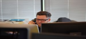 A man talking on a phone in an office.