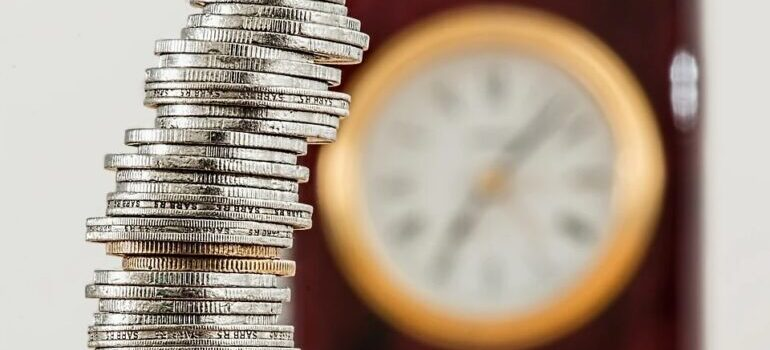 Stacked coins in front of a clock.