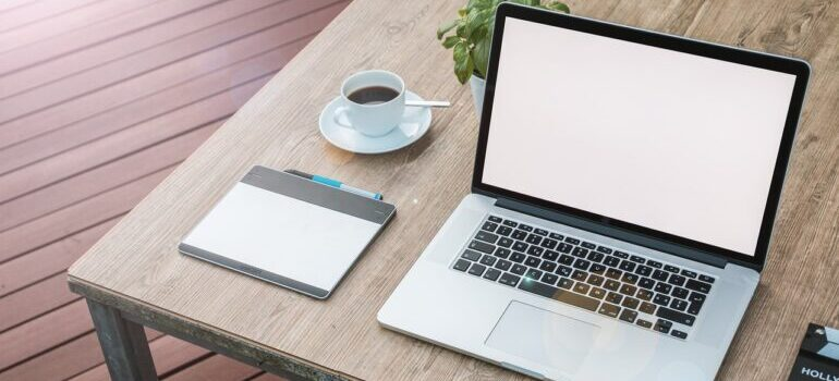a white-screen laptop on a desk next to a cup of coffee