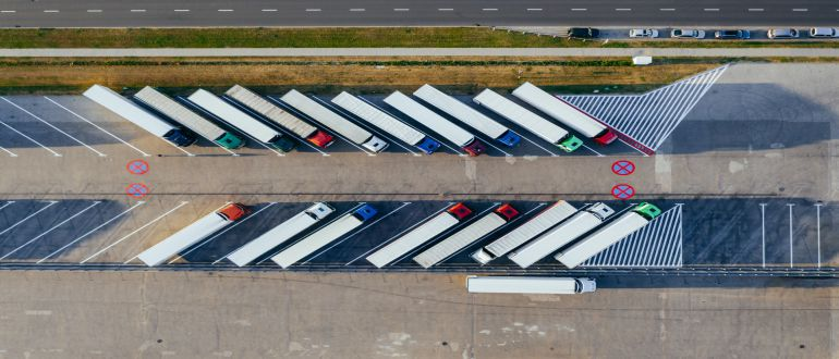 Drone shot of moving trucks on a parking lot.