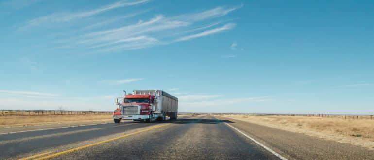 A truck going down a desert highway.