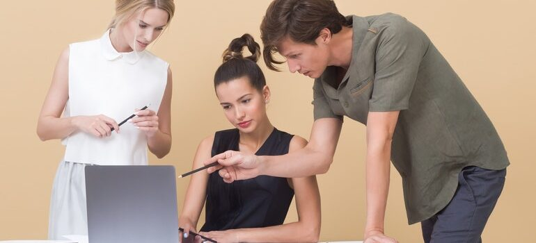 Three people looking at a laptop.
