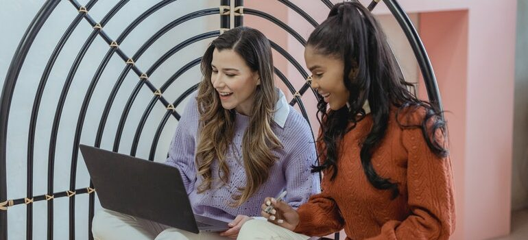 Two women looking at a laptop screen.