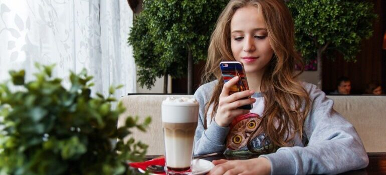 A woman sitting in a coffee shop and looking at her phone.
