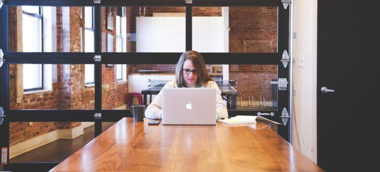 A woman working on a laptop in an office, reading about balancing SEO with quality content.