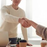 A handshake between a customer and an employee, symbolizing how branding gains customers for your moving business.