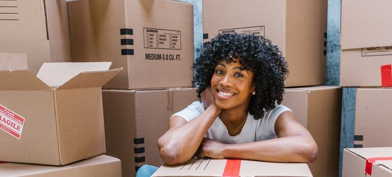A happy woman sitting behind moving boxes and smiling.